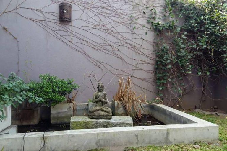 Una fuente de agua con un buda decora el exterior de la propiedad