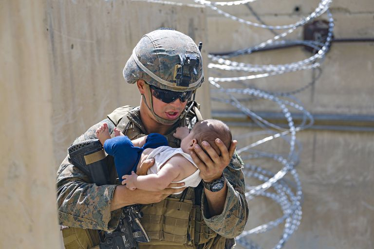 Un marine estadounidense lleva a un bebé durante la evacuación en el aeropuerto Hamid Karzai International Airport