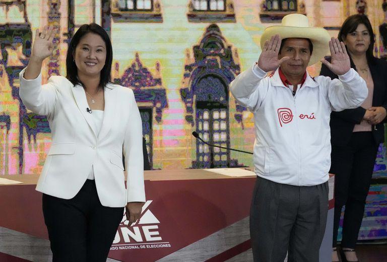 El candidato presidencial del partido Perú Libre Pedro Castillo, derecha, y la candidata Keiko Fujimori, del partido Fuerza Popular, saludan a los periodistas al final del debate presidencial en Arequipa Perú, el domingo 30 de mayo de 2021. Fujimori se enfrenta a Castillo en la final debate de las elecciones presidenciales antes de las elecciones del 6 de junio. (AP Foto/Martin Mejia)