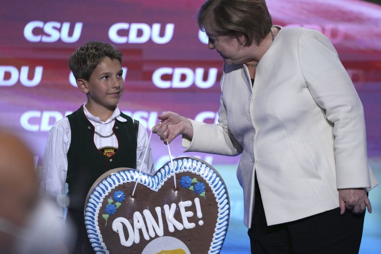 Un chico bávaro le entrega un regalo de agradecimiento a la canciller Angela Merkel por su gestión de gobierno
