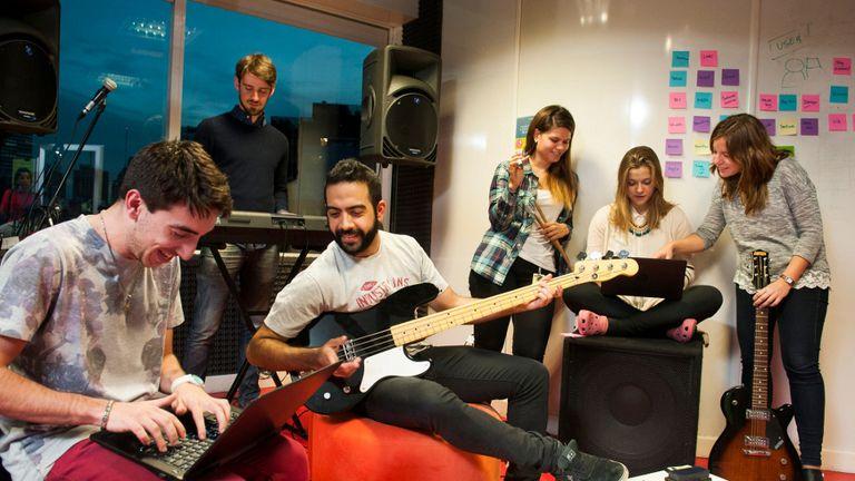Francisco Márquez toca el bajo junto a sus compañeros de trabajo en la sala de música de Globant