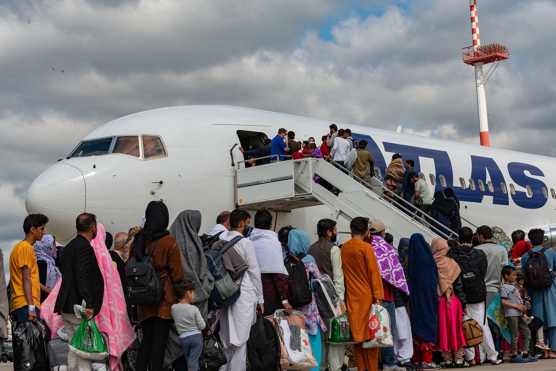 Refugiados afganos abordan un avión comercial con destino a EE. UU. Desde Kabul en la base aérea de Ramstein, en Alemania, después de ser evacuados de Afganistán tras la toma de poder de los talibanes