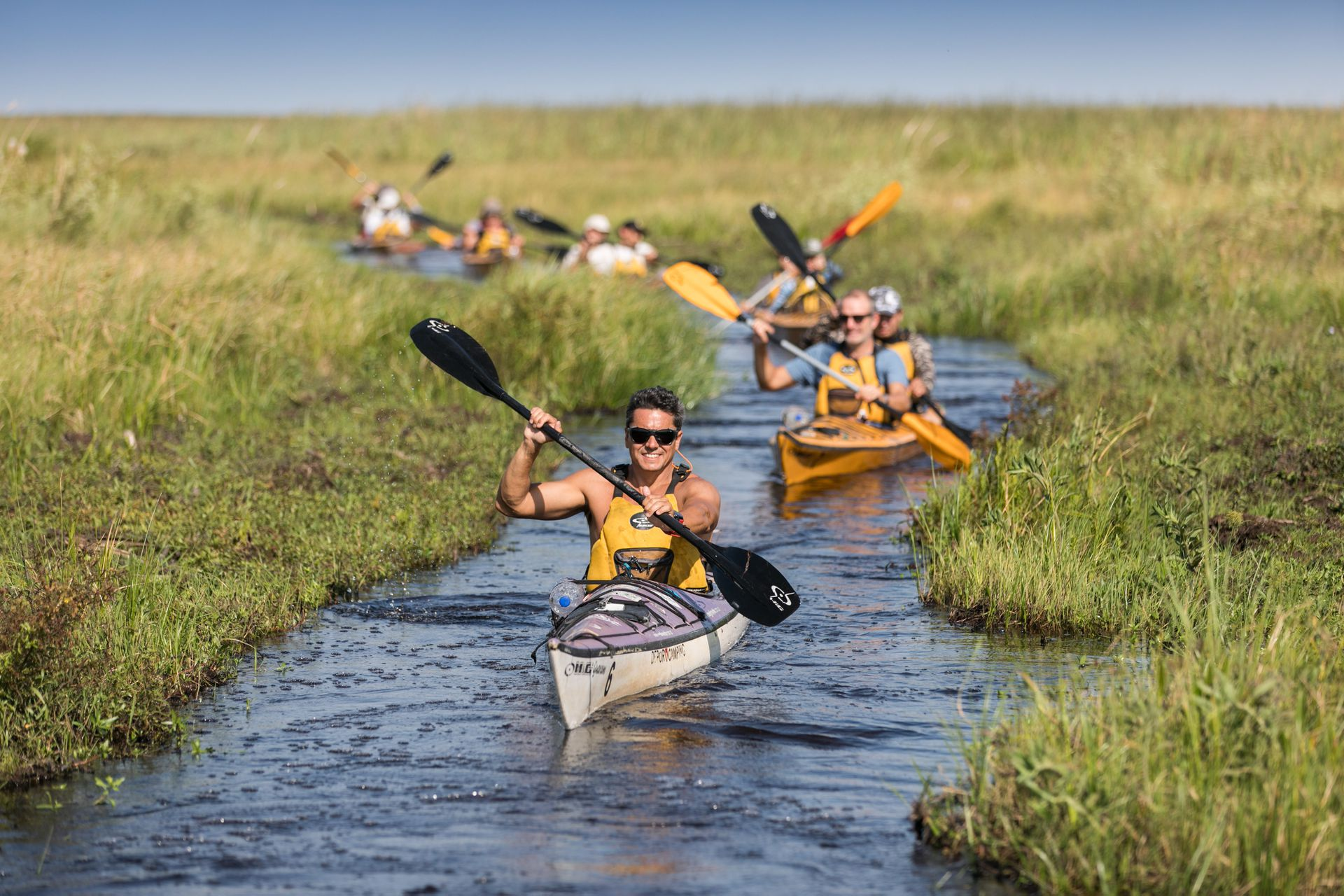 Los kayaks avanzan en fila india por un estrecho canal.