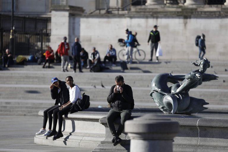 La gente se relaja en Trafalgar Square en Londres el 25 de marzo de 2020, después de que el gobierno de Gran Bretaña ordenó un cierre para frenar la propagación del nuevo coronavirus