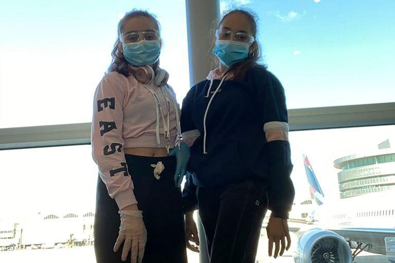Dos de las chicas posan después de haber pasado los controles de seguridad y sanitarios, horas antes de subir al avión de Aerolíneas Argentinas
