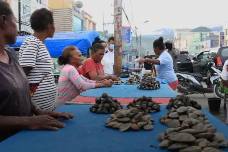Las mujeres venden las almejas en los mercados locales