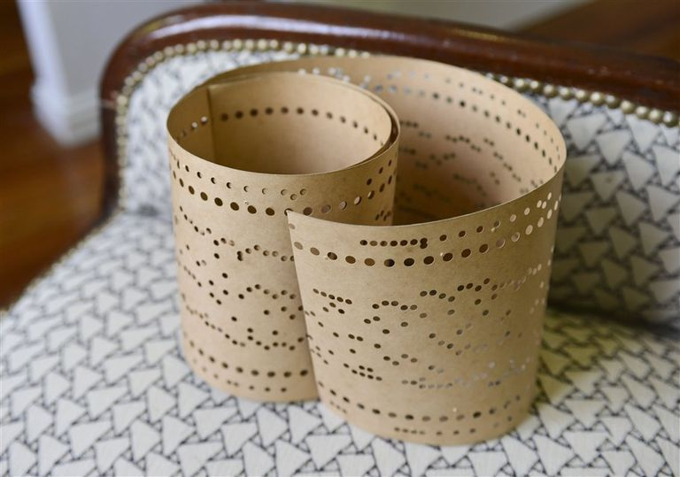 Objetos musa. Sobre un sillón tapizado con sus telas y dibujos, un viejo rollo de cartón perforado, utilizado para grabar los programas de dibujos que luego se transforman en bordados de broderie o guipures, que atesora