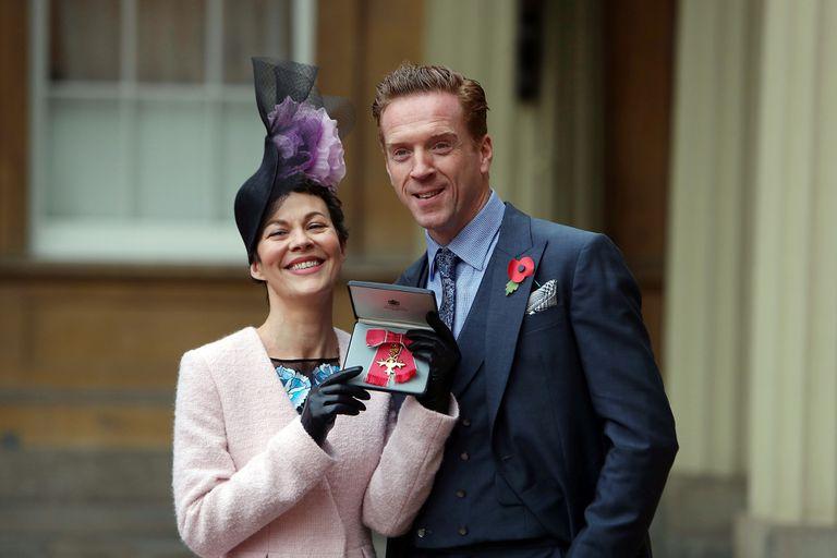 Helen McCrory y su esposo Damian Lewis en el palacio de  Buckingham cuando fue condecorada por la reina por su contribución a las artes escénicas