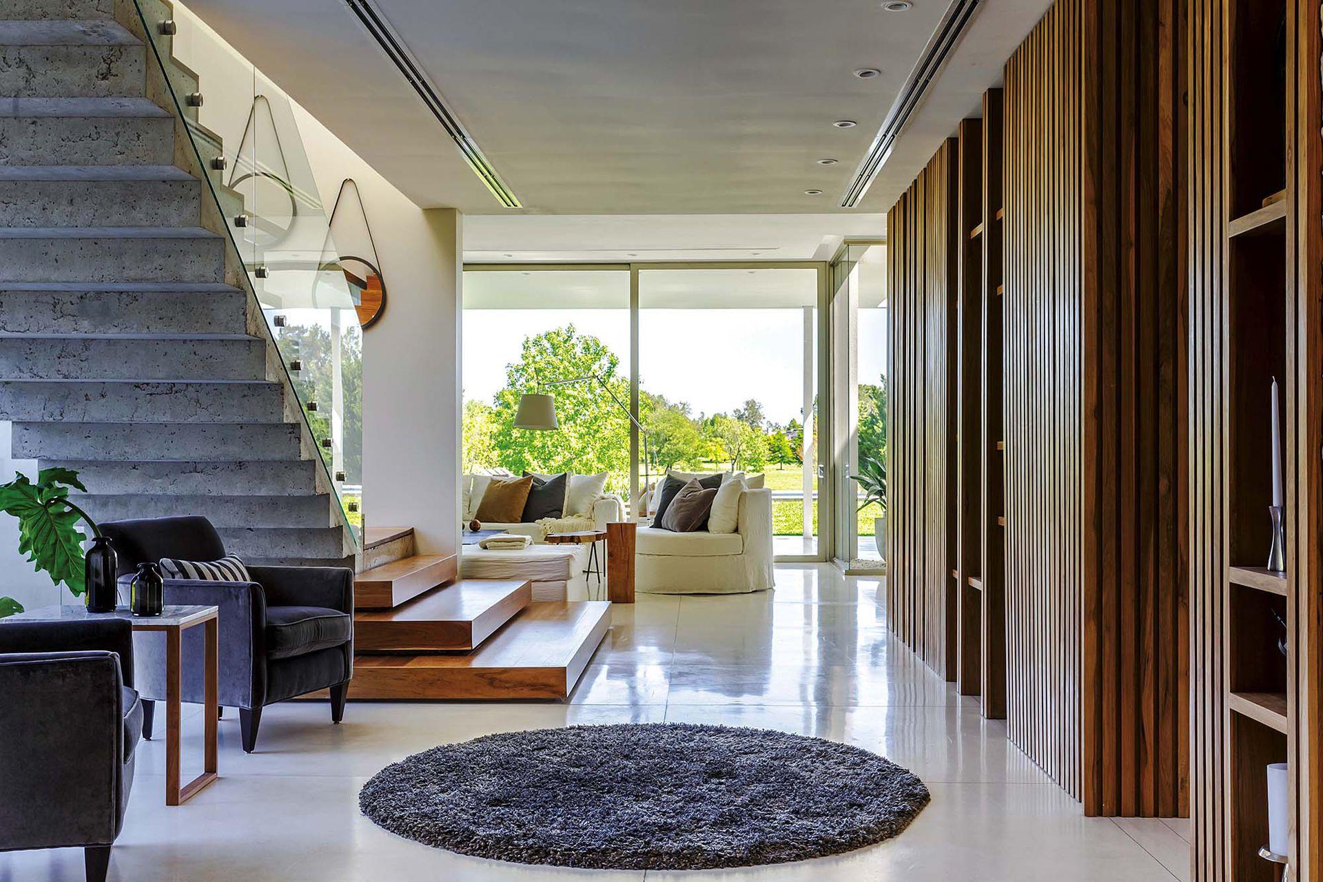 A un lado del hall, mueble divisor en petiribí (Fernando Moy) con espacios de guardado y columnas que se van separando gradualmente a medida que avanzan hacia el ventanal. Dentro de su estructura hay una puerta oculta hacia la cocina.