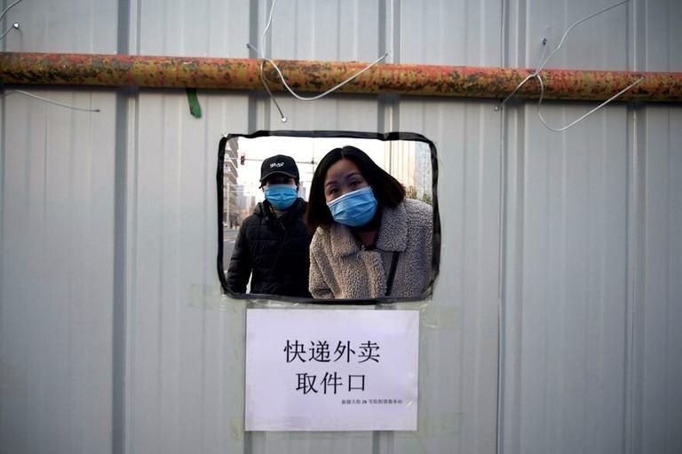 La gente espera su pedido dentro de un área con barricadas en el distrito Daxing de Pekín el 21 de enero de 2021, después de que se impusiera un cierre parcial en la capital china por el avance del coronavirus