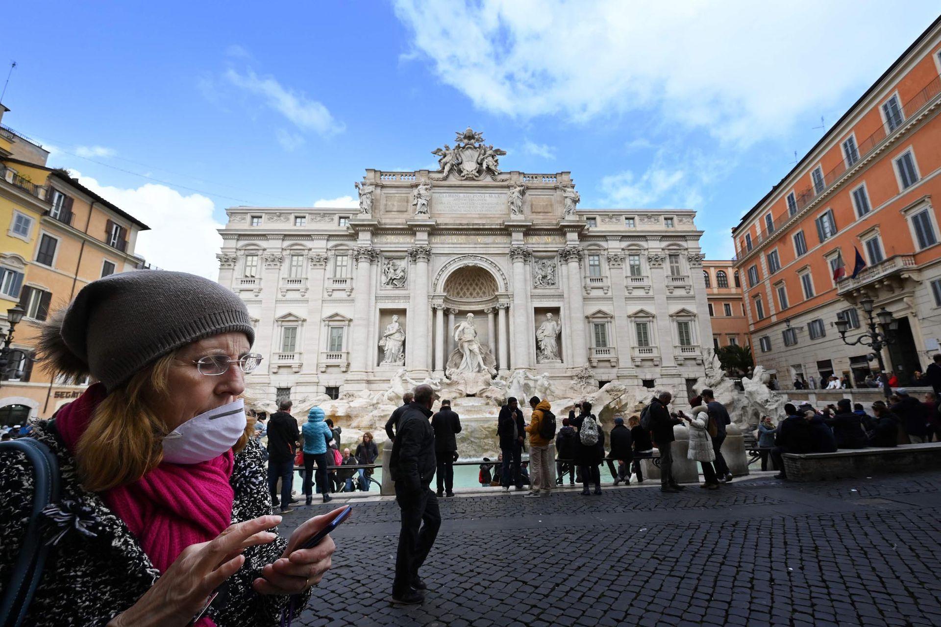 Un turista usa un barbijo mientras camina frente a la Fontana de Trevi en el centro de Roma, el 3 de marzo de 2020.