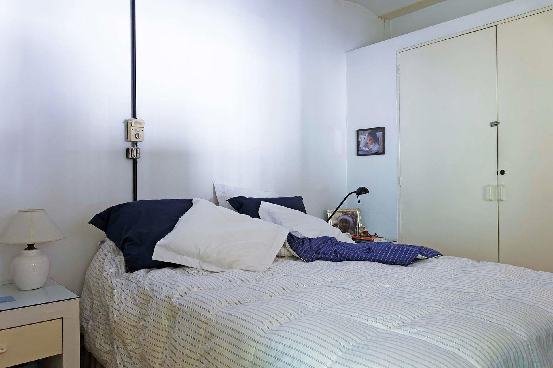 En la planta alta está la suite principal. El ambiente se resolvió con pocos elementos: ropa de cama en blanco, mesas de luz a tono, y almohadones en negro para contrastar.