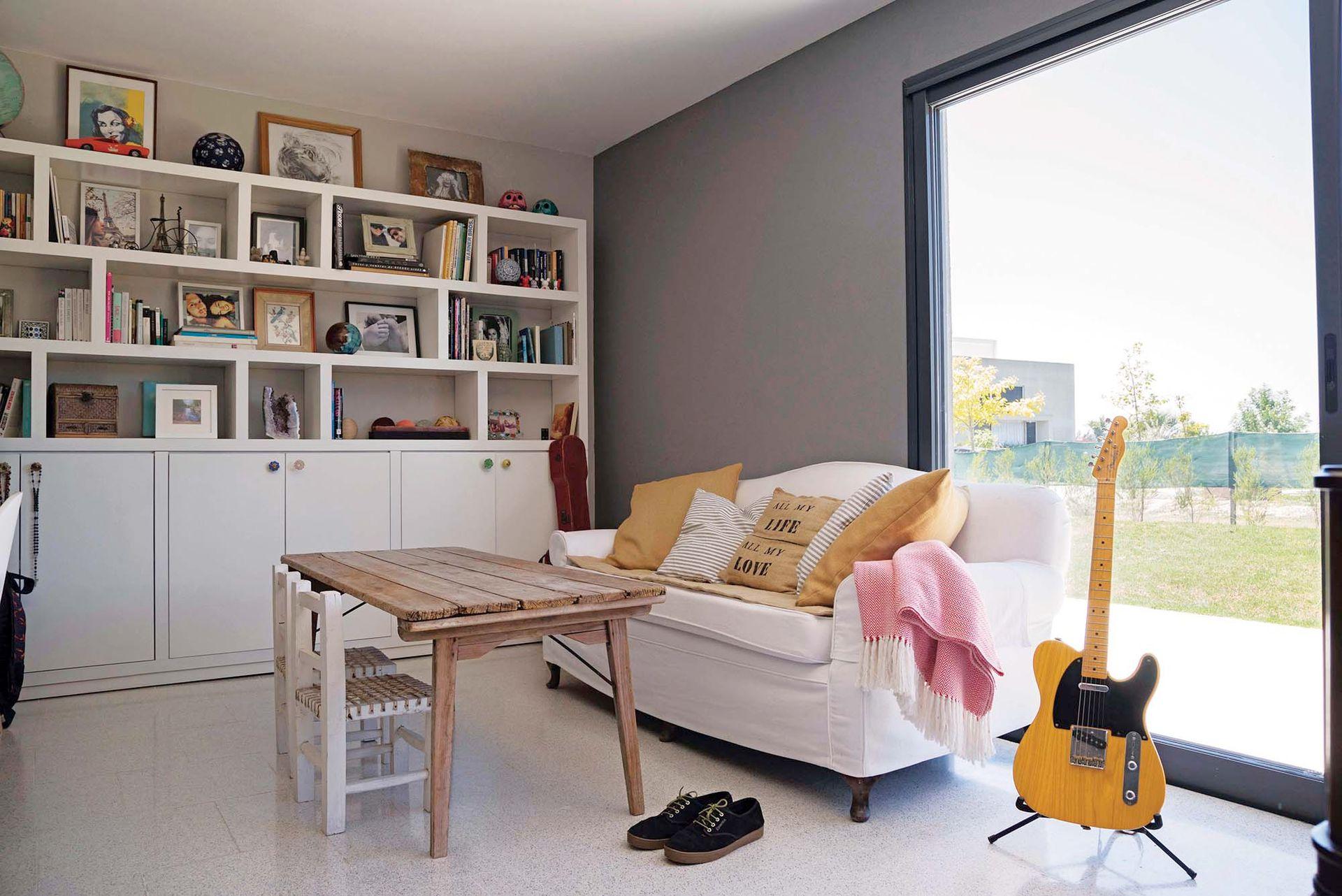 En el playroom, un sofá heredado; sillitas materas traídas de Salta y una biblioteca de pared a pared, diseño del dueño.