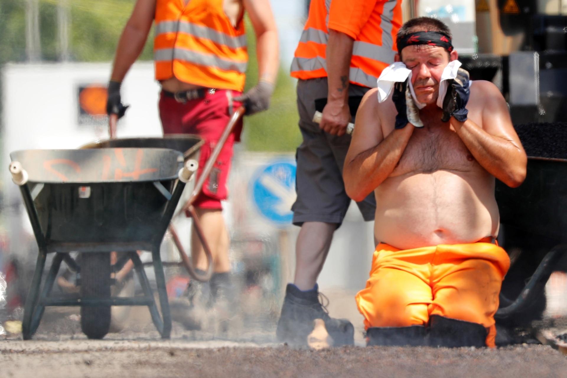 Un trabajador de la construcción se limpia la cara , mientras que las temperaturas alcanzan nuevos máximos históricos en Berlín, Alemania