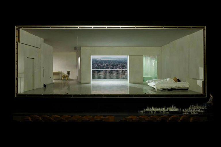 Un living, una cama, un baño y la ciudad al fondo
