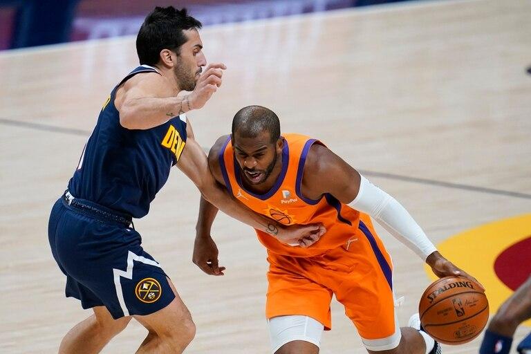 El jugador de los Suns de Phoenix Chris Paul (derecha) elude la marca de su rival de los Nuggets de Denver Facundo Campazzo, en la primera mitad del juego de la NBA que enfrentó a ambos equipos, el 1 de enero de 2021, en Denver.