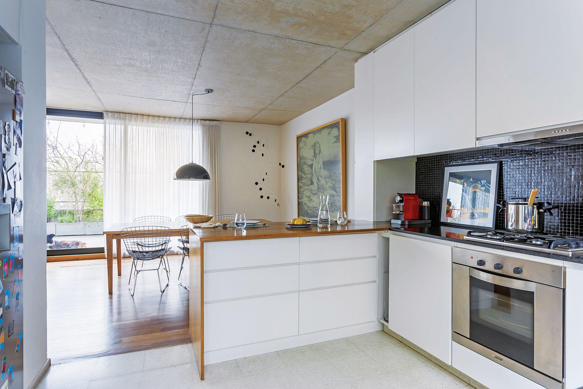 En la cocina, el mobiliario con frente de madera laqueada y sin herrajes crea un plano neto y continuo. En el sector se puso una alzada de venecitas y cocina (Indesit).