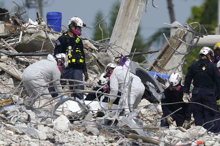 Rescatistas levantan una lona que contiene restos humanos recogidos en el sitio del edificio residencial derrumbado Champlain Towers South en Surfside, Florida, 5 de julio de 2021. (AP Foto/Lynne Sladky)