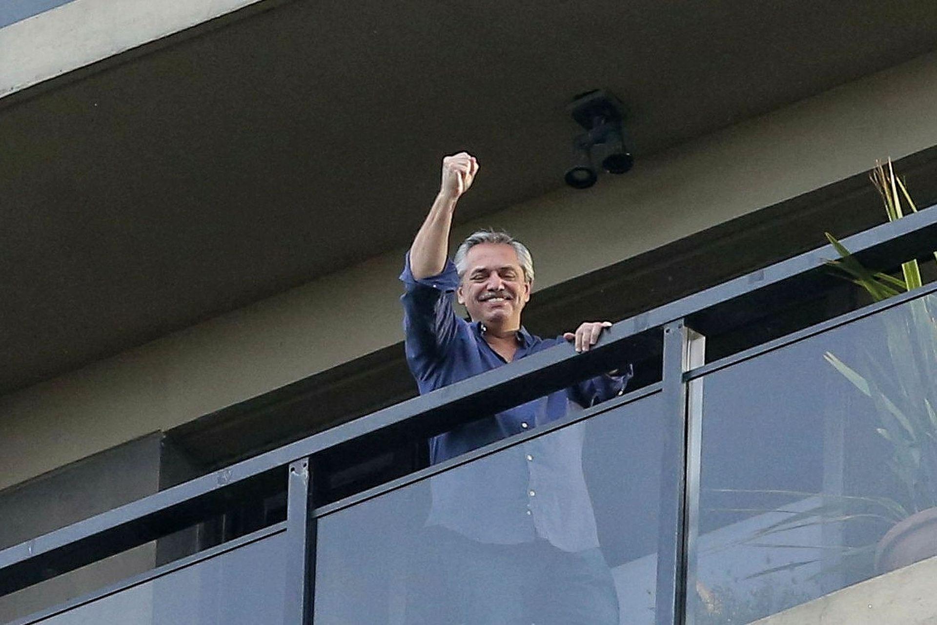 Alberto Fernández saluda desde el balcón de su departamento en el barrio porteño de Puerto Madero, tras el anuncio de Cristina de su candidatura presidencial, el 15 de mayo de 2019