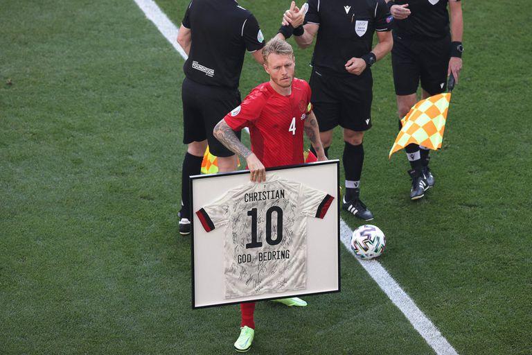 El defensor danés Simon Kjaer sostiene una camiseta enmarcada del mediocampista danés Christian Eriksen antes del inicio del partido de fútbol del Grupo B de la UEFA EURO 2020 entre Dinamarca y Bélgica en el Estadio Parken de Copenhague el 17 de junio de 2021 (Foto de HANNAH MCKAY / POOL / AFP). )
