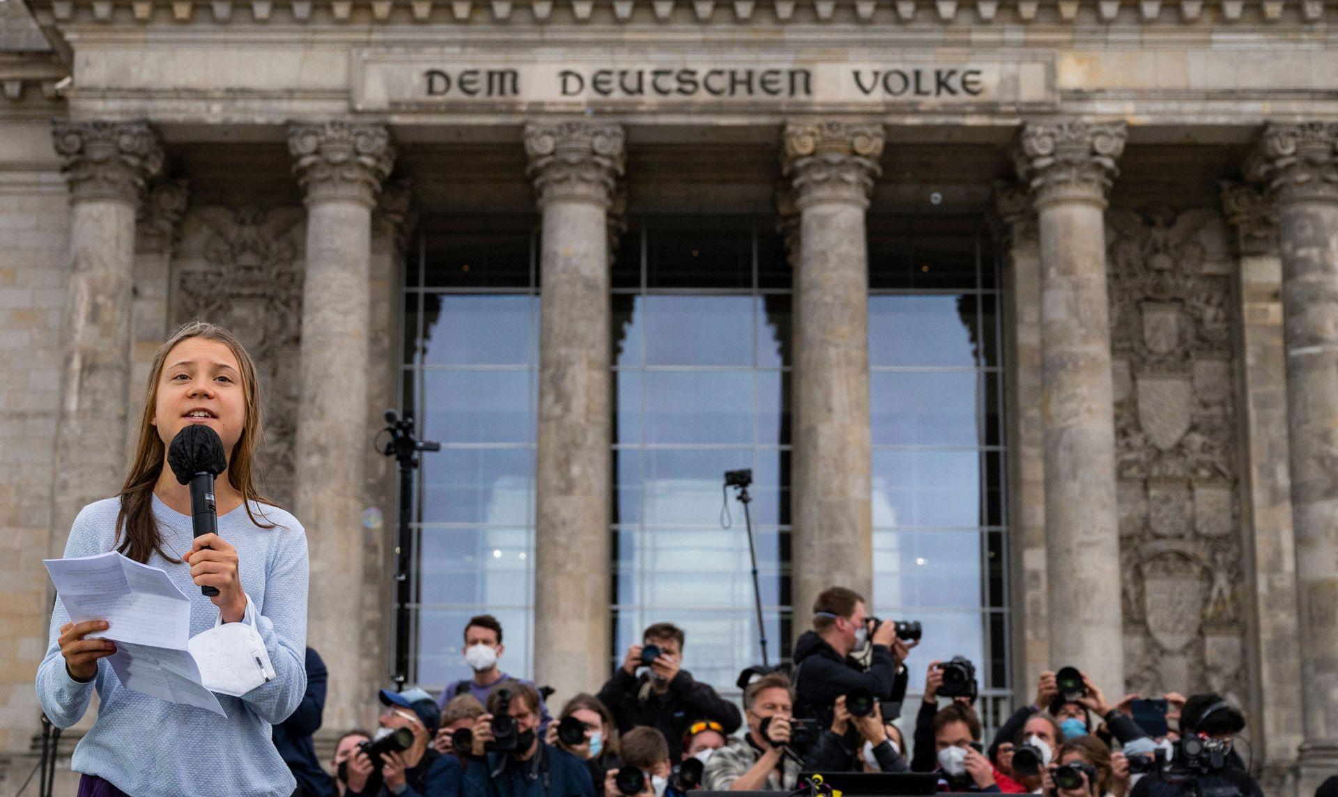 La activista climática sueca Greta Thunberg, frente al edificio del Reichstag, se dirige a los manifestantes que participan en una huelga climática global de Fridays for Future en Berlín el 24 de septiembre de 2021