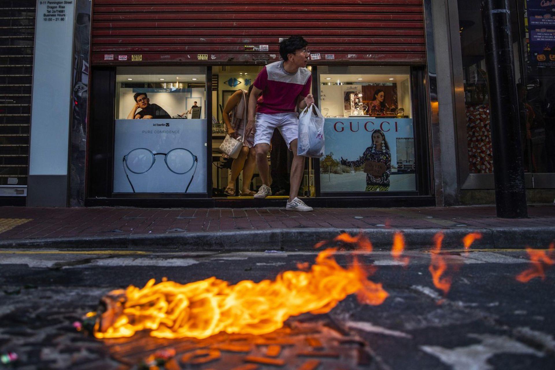 Varios clientes salen de un óptica mientras una molotov se prende fuego en medio de la calle