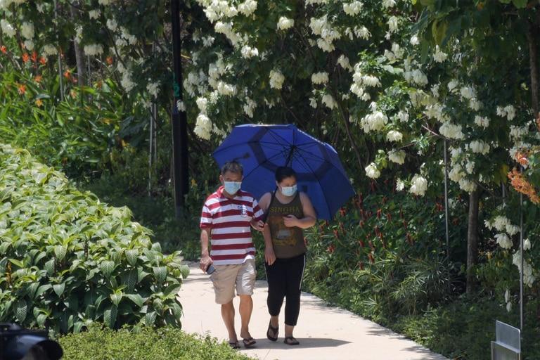 Una pareja con máscaras, en medio de la preocupación por la propagación del nuevo coronavirus, camina por un parque en Singapur el 24 de marzo de 2020