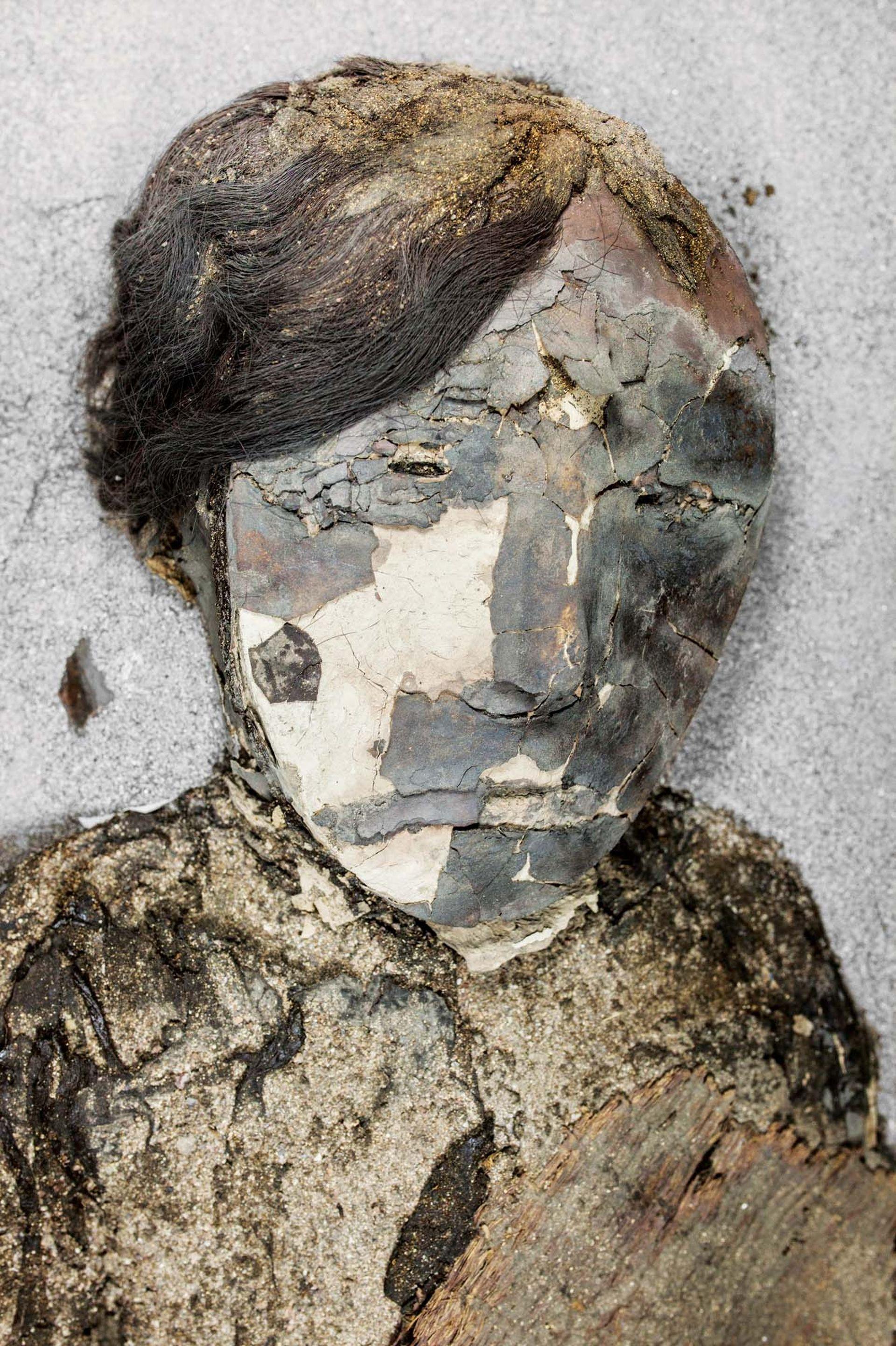 Una de las llamadas momias negras, cubierta con una oscura capa de óxido de manganeso.