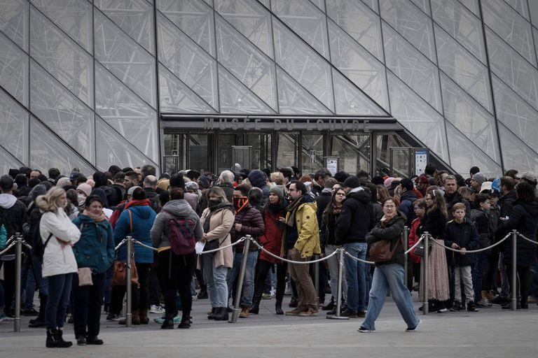 Visitantes formando fila en la entrada principal para ingresar al Museo del Louvre