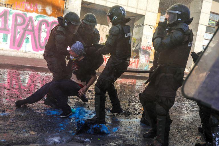 Un manifestante es detenido ayer en otra jornada de protestas en Santiago