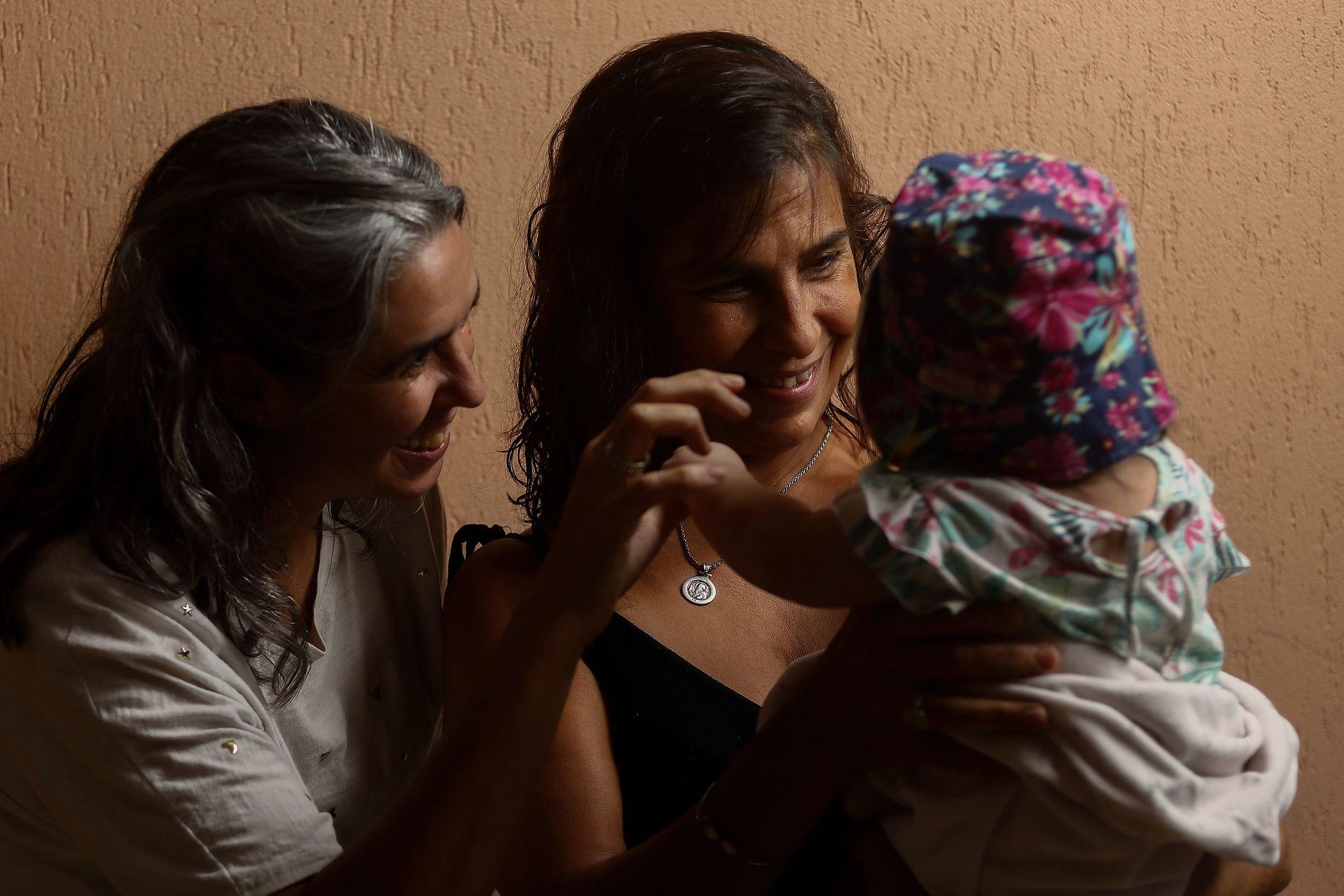 Marcela (de negro) y Micaela comparten con sus familias la tarea de cuidar a la pequeña beba de forma transitoria; integran Comunidad Malú, una organización social de familias de abrigo de La Plata