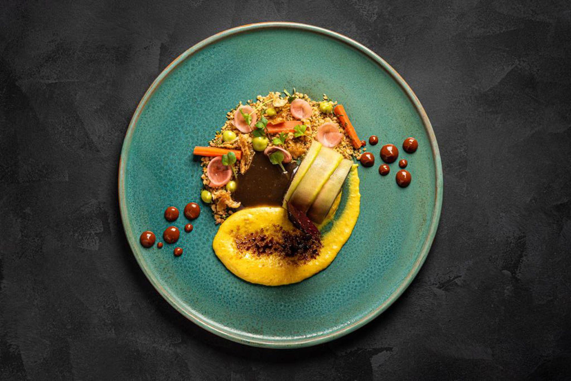 Pollo campestre relleno con mousseline de hongos, sobre emulsión de maíz caramelizada con azúcar mascabo, acompañado de cuscús de piñones asados y vegetales encurtidos.