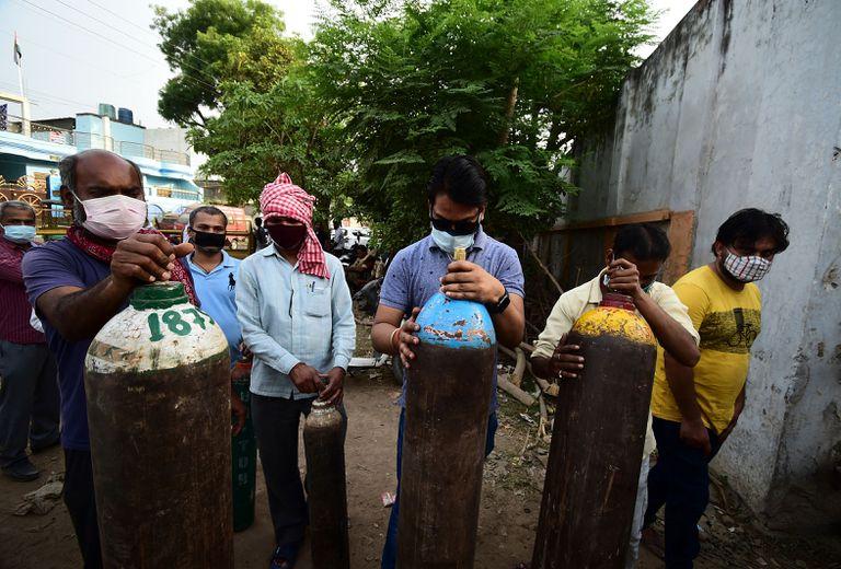 Pese a ser líder en inmunización e importante productor de vacunas, en India escasea el oxígeno. Un grupo de personas hace fila para cargar tubos de oxígeno en una estación en Allahabad el 20 de abril de 2020