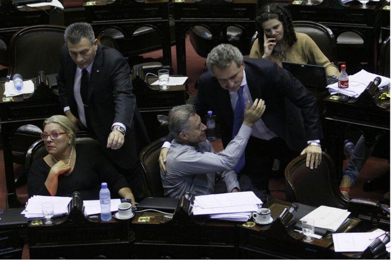 La diputada de la Coalición Cívica Elisa Carrió, lejos del jefe del bloque kirchnerista Agustín Rossi, que festeja la victoria del oficialismo en la Cámara baja