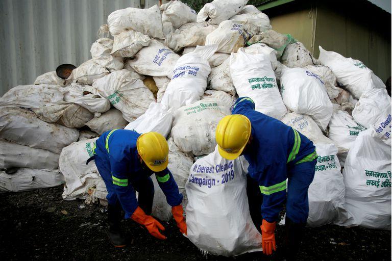 Trabajadores de una empresa de reciclaje cargan la basura recolectada y traída del monte Everest en Katmandú, Nepal