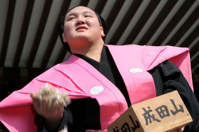 """Munkhbat Davaajargal, apodado """"Hakuho"""", arroja paquetes de porotos en Narita, Japón; se cree que ese hábito ahuyenta la desgracia y trae buena suerte."""