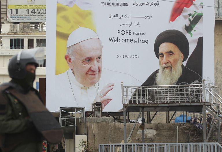 Un soldado iraquí en guardia junto a un cartel de Francisco y el gran  ayatollah Ali Sistani en el centro de Bagdad, la capital iraquí, una ciudad y un país con un pasado reciente bañado en sangre