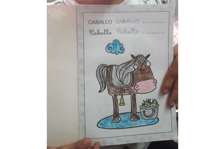 Ciro sostiene un dibujo que hizo para la escuela; le encanta los animales