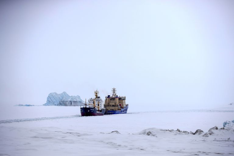 Un rompehielos que abre el camino para un carguero con un iceberg al fondo cerca de un puerto en la isla Alexandra Land