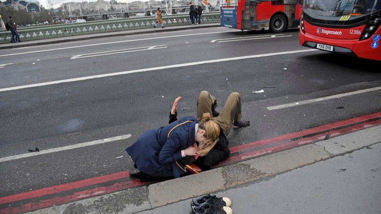 Un nujer asiste a un hombre lesionado durate un ataque en el puente Westminster en Londres, 22 de marzo