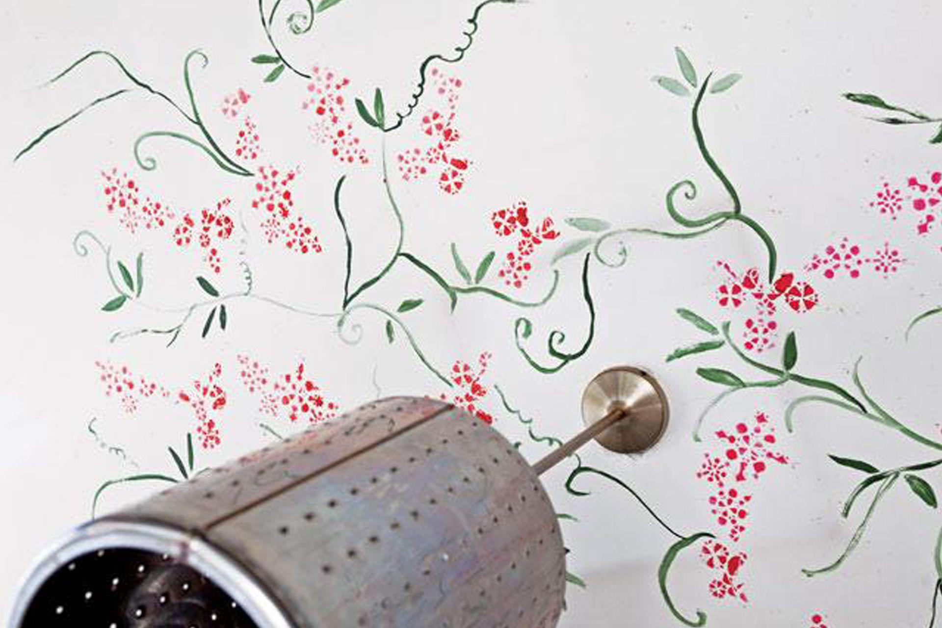 Flores pintadas rodean la lámpara que antes fue tambor de lavarropas.
