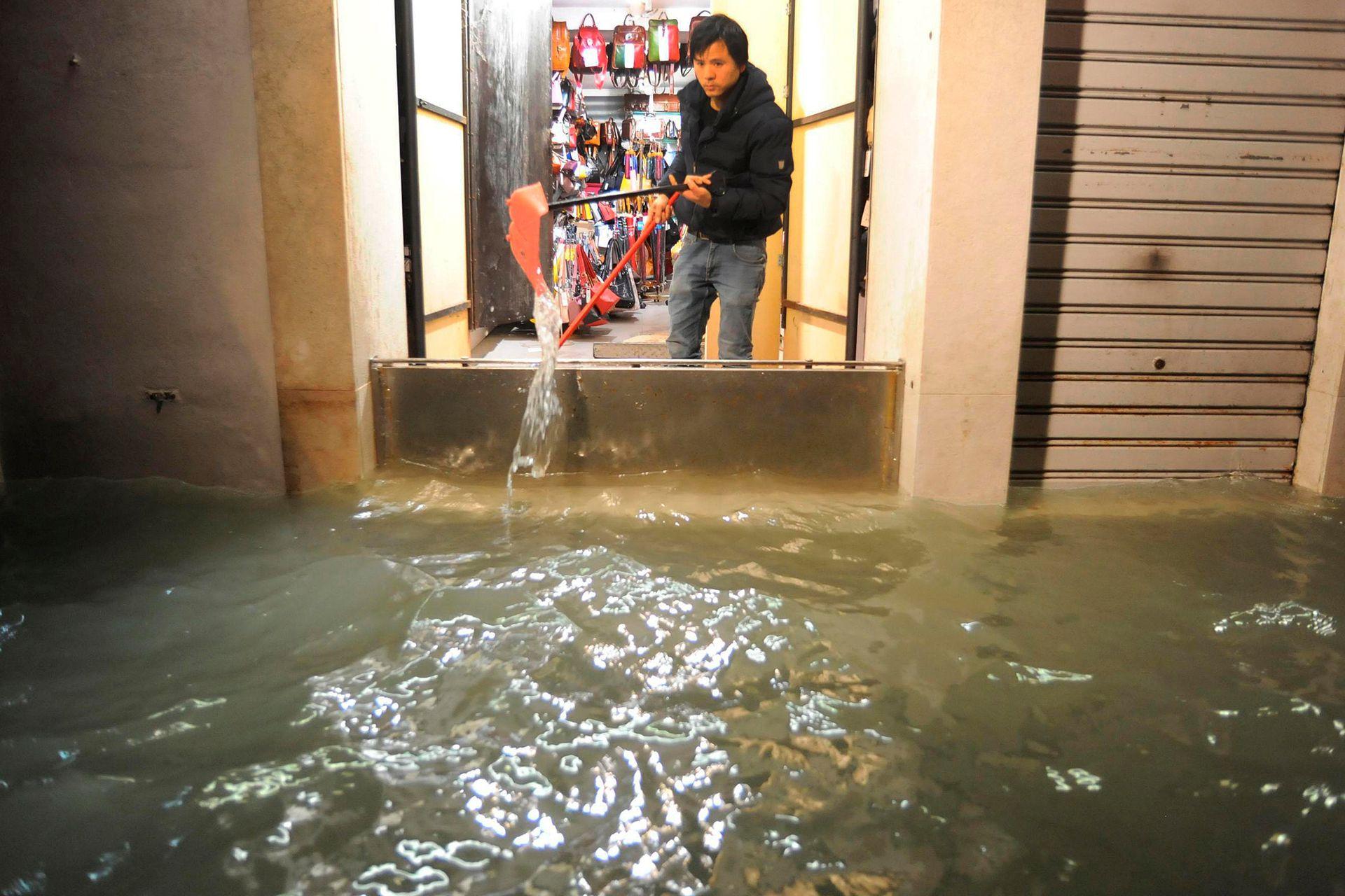 Un hombre saca el agua de un comercio luego de que la compuerta no resistiera la inundación, ya que la altura superó el promedio habitual.