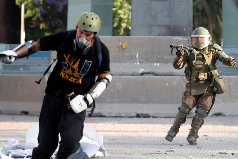 La policía lanza un proyectil a un manifestante durante las protestas en Chile