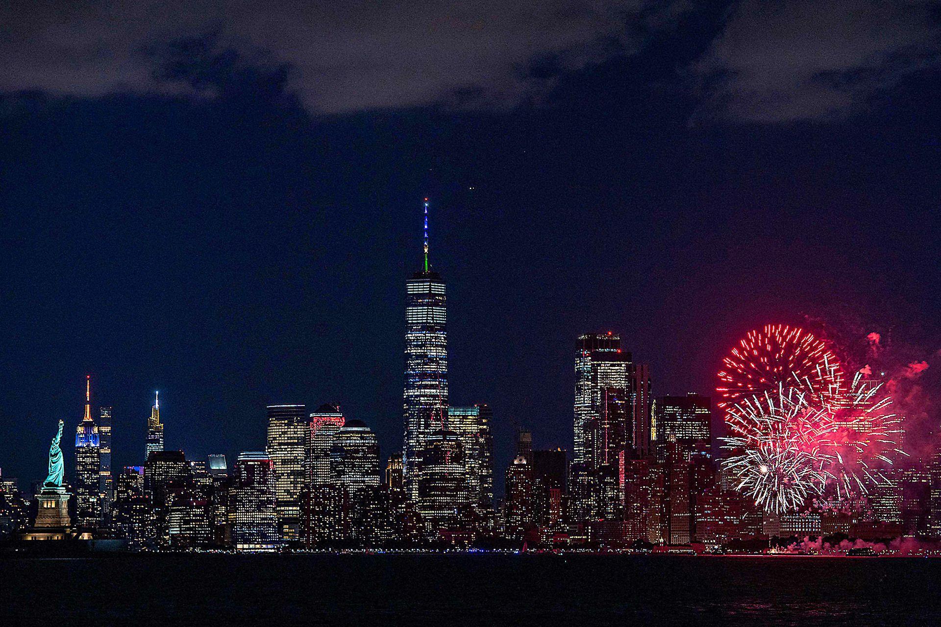 La Estatua de la Libertad (izquierda) y el horizonte de Nueva York se ven mientras los fuegos artificiales estallan en el puerto de esa ciudad durante la celebración por llegar al 70 por ciento de los adultos que recibieron su primera dosis de la vacuna Covid-19, el 15 de junio de 2021