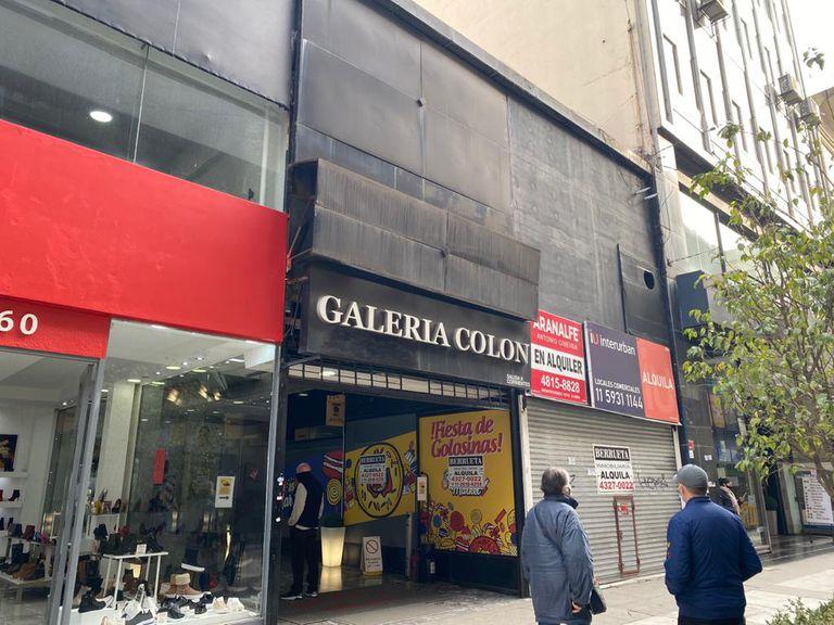 """Un """"arbolito"""" se acerca a una mujer frente a la Galería Colón cerrada, en la calle Florida."""