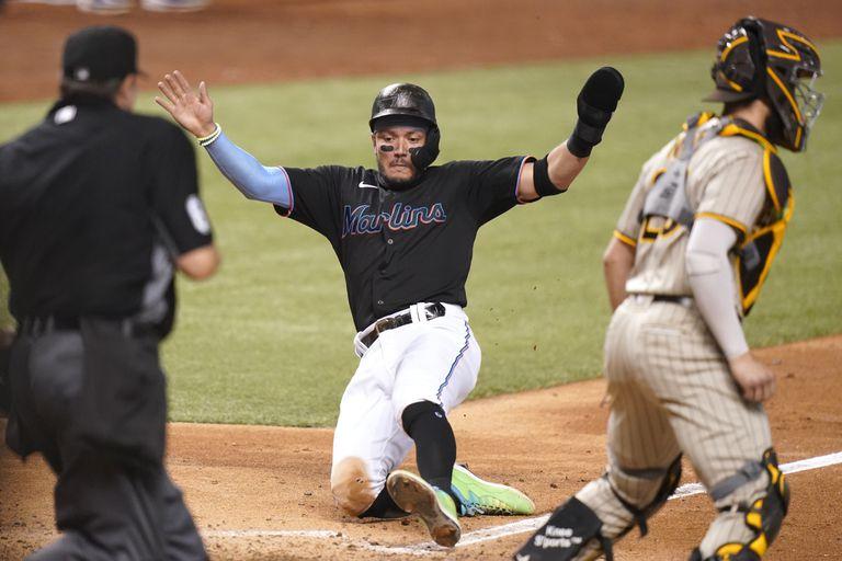 Miguel Rojas, de los Marlins de Miami, centro, anota con sencillo de Jesús Aguilar durante la séptima entrada del juego de beisbol contra los Padres de San Diego, el sábado 24 de julio de 2021, en Miami. (AP Foto/Lynne Sladky)