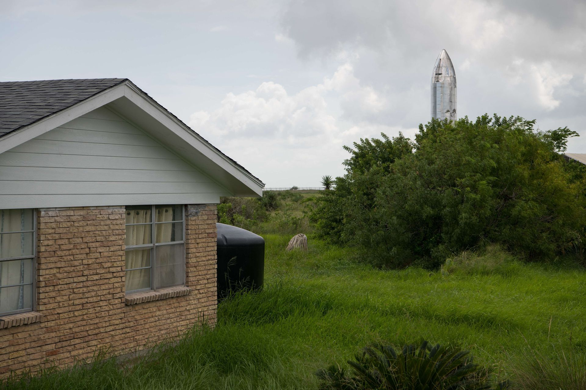 Un prototipo de la nave espacial Starship de SpaceX se muestra detrás de una casa en Boca Chica Village