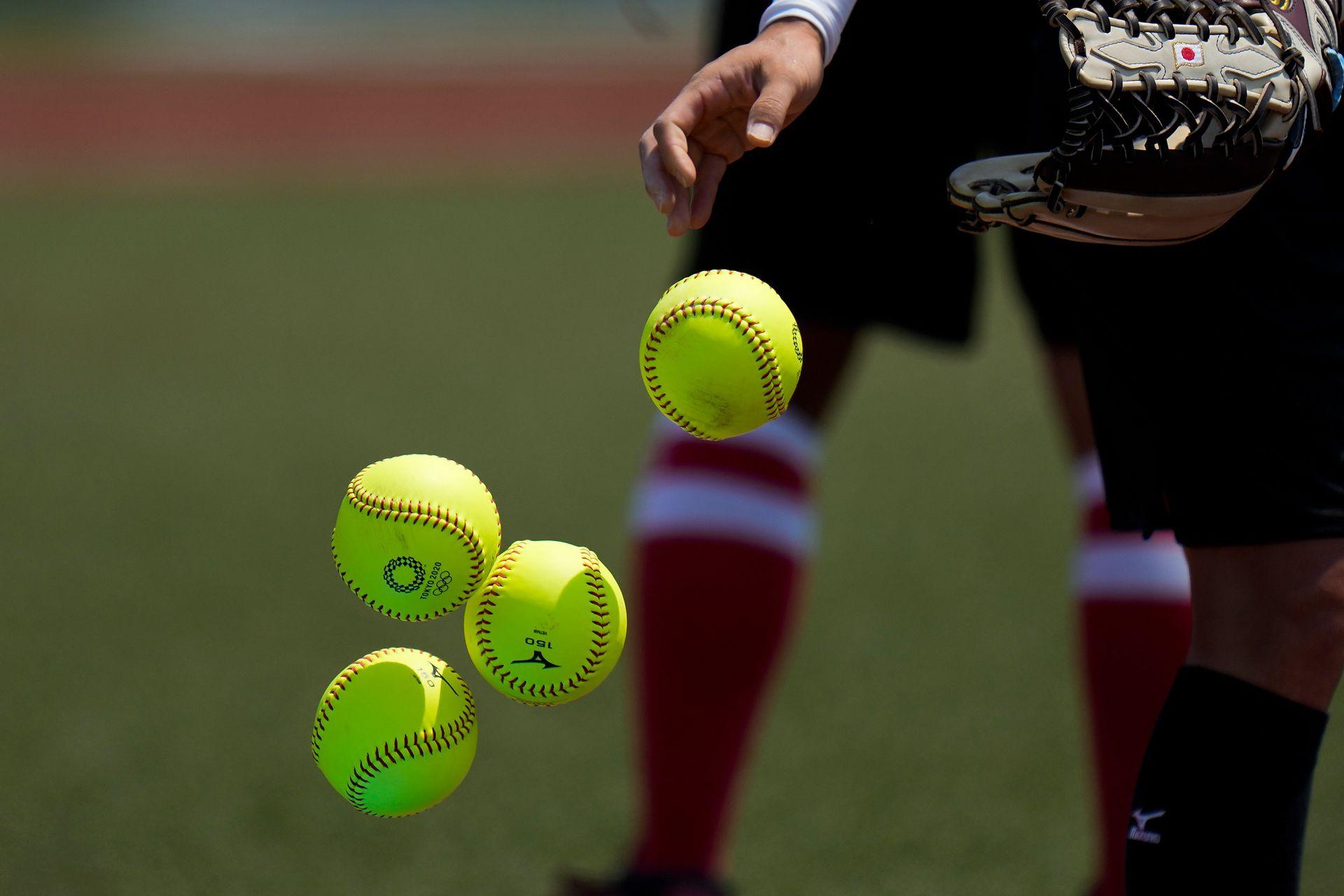 Una jugadora japonesa de softball tira pelotas dentro de una canasta durante una práctica en el estadio Azuma de Baseball.
