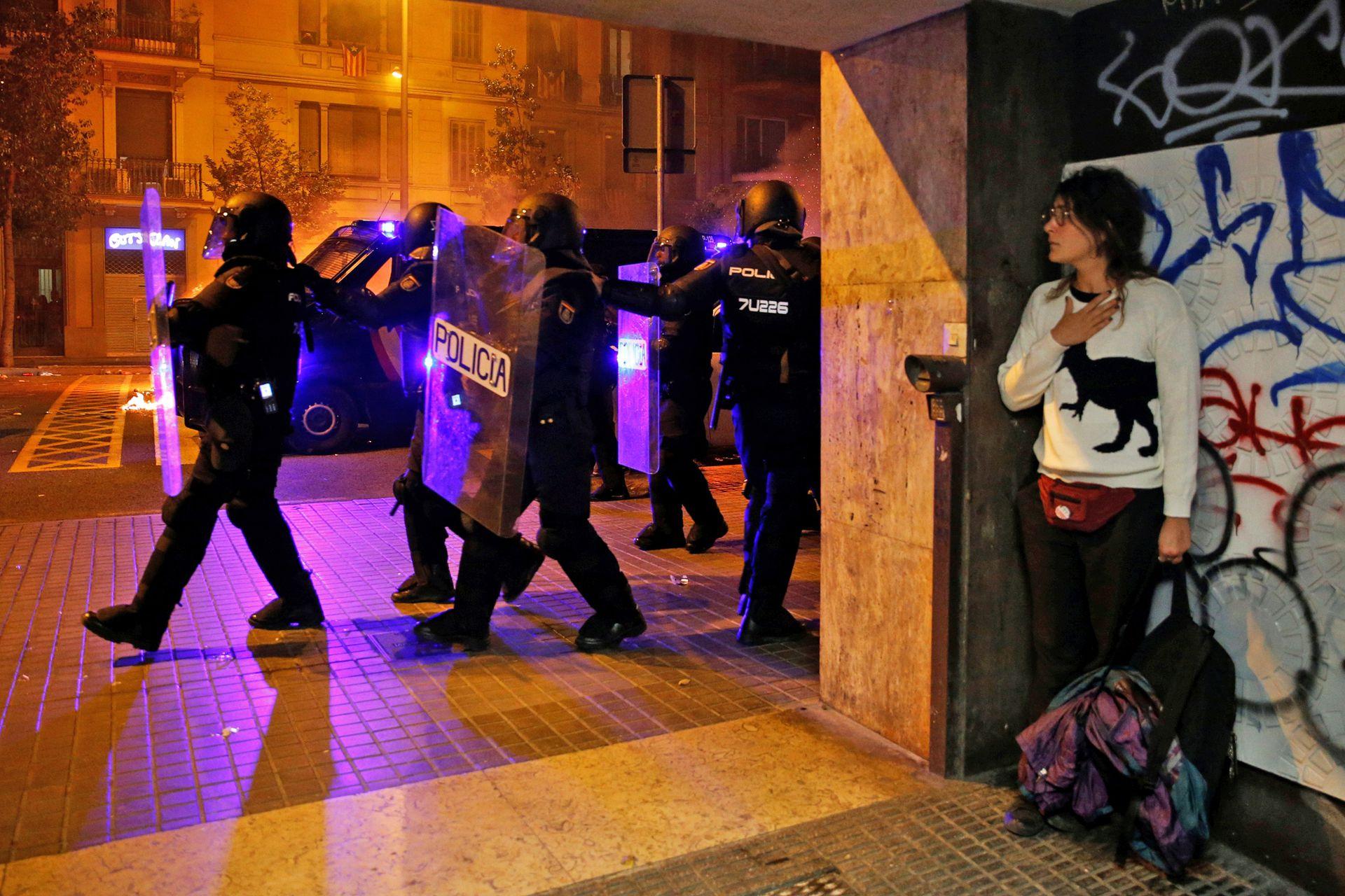 """Hubo """"al menos una veintena de personas detenidas"""" en toda Cataluña, tras los 51 de la víspera, indicaron los Mossos. Cuatro ingresaron en prisión sin fianza por atentado a la autoridad y desórdenes."""