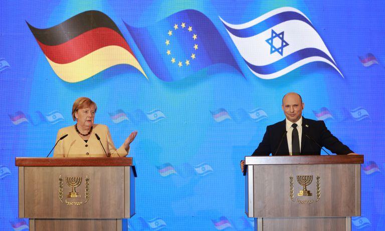 La canciller de Alemania, Angela Merkel, y el primer ministro de Israel, Naftali Bennett, ofrecen una conferencia de prensa conjunta tras una reunión en el Hotel Rey David de Jerusalén, el domingo 10 de octubre de 2021. (Menahem Kahana/Pool via AP)